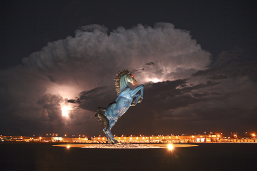 a large blue demon horse next to the Denver International Airport